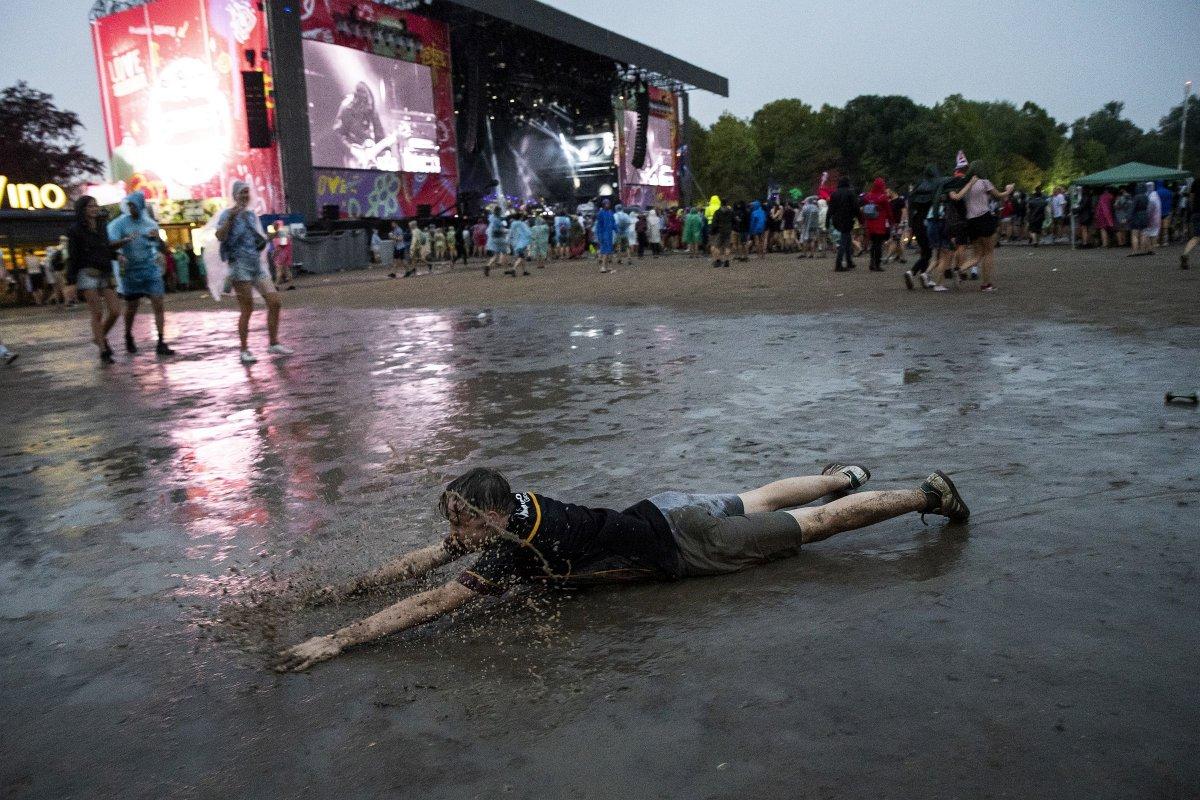 Fesztiválozó fekszik a sárban a felhőszakadás után az amerikai The War on Drugs együttes koncertje közben <span class=