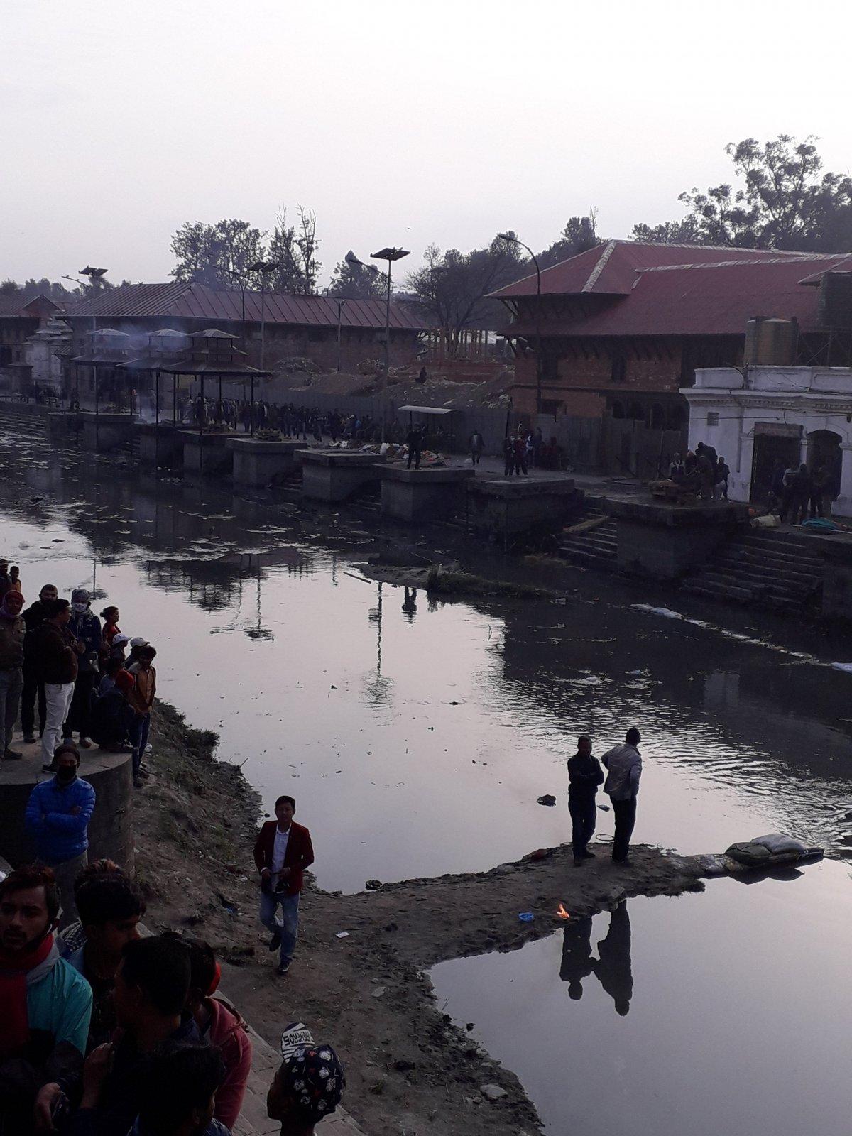 Katmanduban a folyó partján tartják a rituális halottégetéseket, a kiszögellésekben állnak a máglyák. Égetés után a vízbe öntik a hamvakat •  Fotó: Kiss Judit