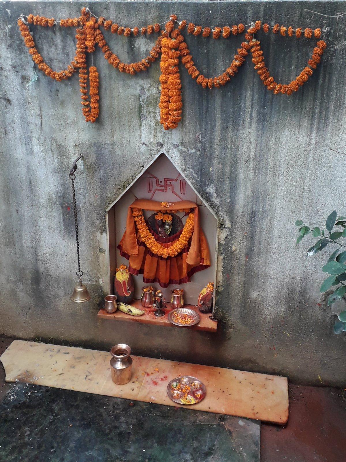 Rizs, banán, virágszirmok- és füzérek a Siva isten tiszteletére állított kis szentélynél egy katmandui szálloda udvarán •  Fotó: Kiss Judit