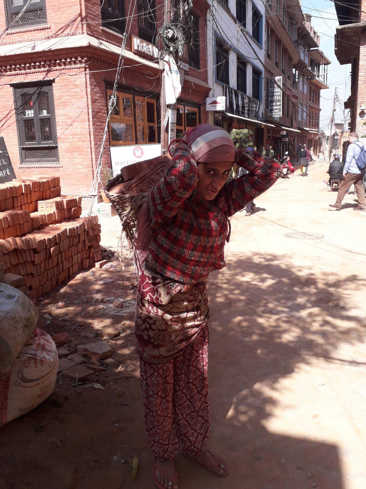 Nem ritka Nepálban, hogy nők cipelik a fejükhöz erősített kosarakban a téglát •  Fotó: Kiss Judit